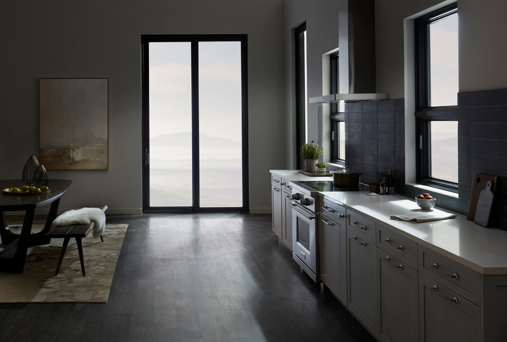 Dark and contemporary kitchen with black sliding patio door and a wall of cabinets with awning windows above