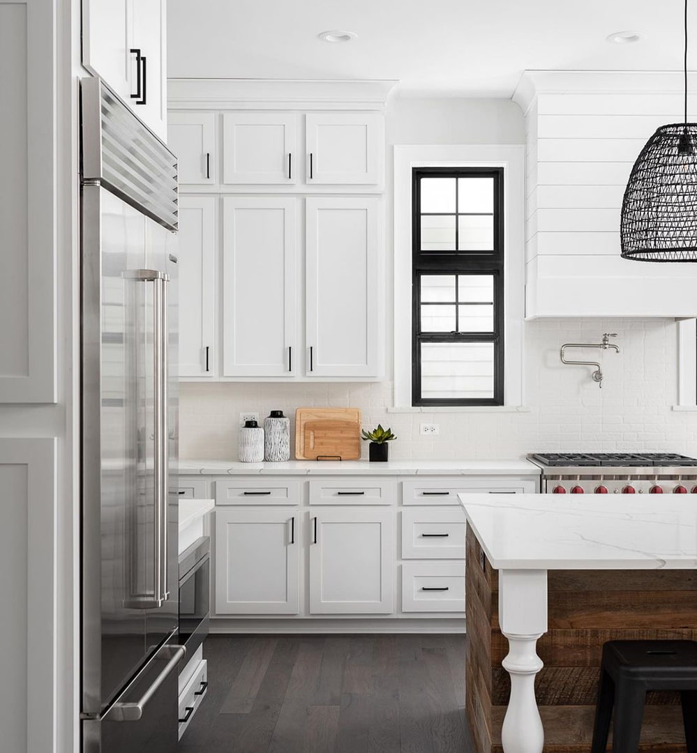 A white farmhouse kitchen has a black picture window stacked on a black double-hung window.