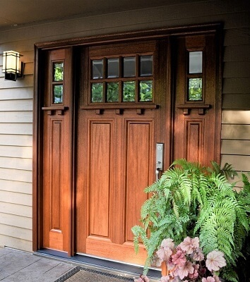 Mahogany stained wood front door with sidelights on craftsman home