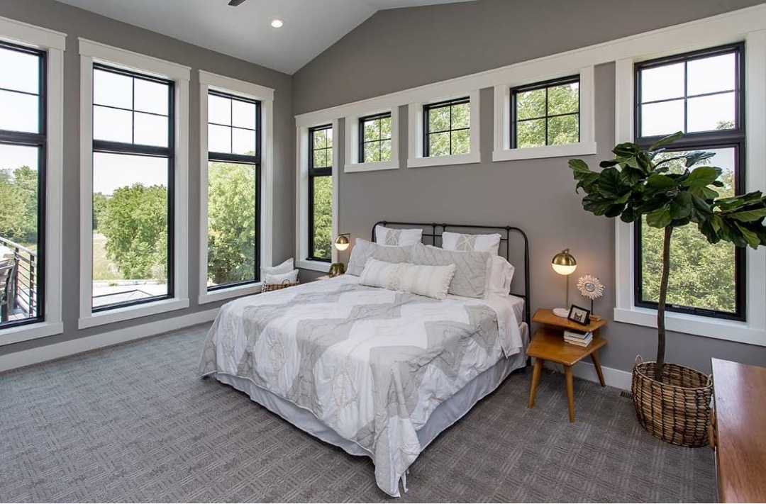 contemporary bedroom with black window frames and white wood trim