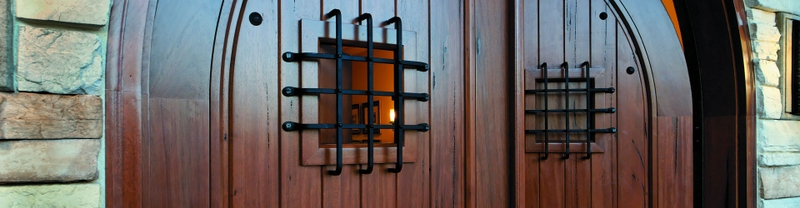 close shot of a solid wood entry door with square speakeasy with grilles