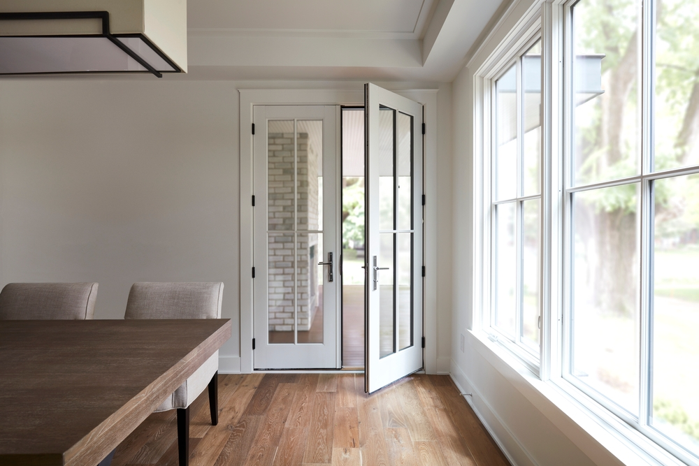 White farmhouse style dining room with wood flooring, double-hung windows on the right, and a set of white french doors open