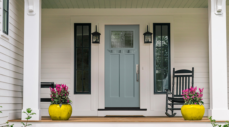 Frost blue entry door of white craftsman style home