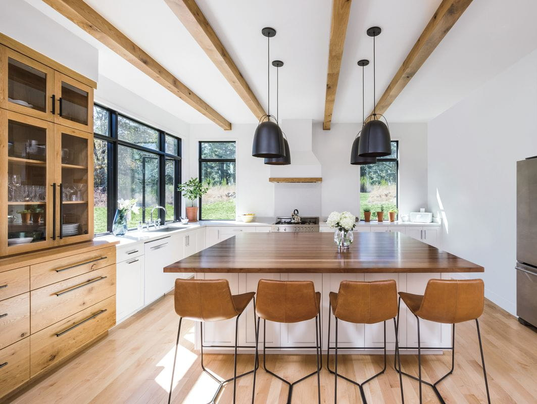 Light-filled kitchen with wood and white cabinetry, black windows and large wood island.