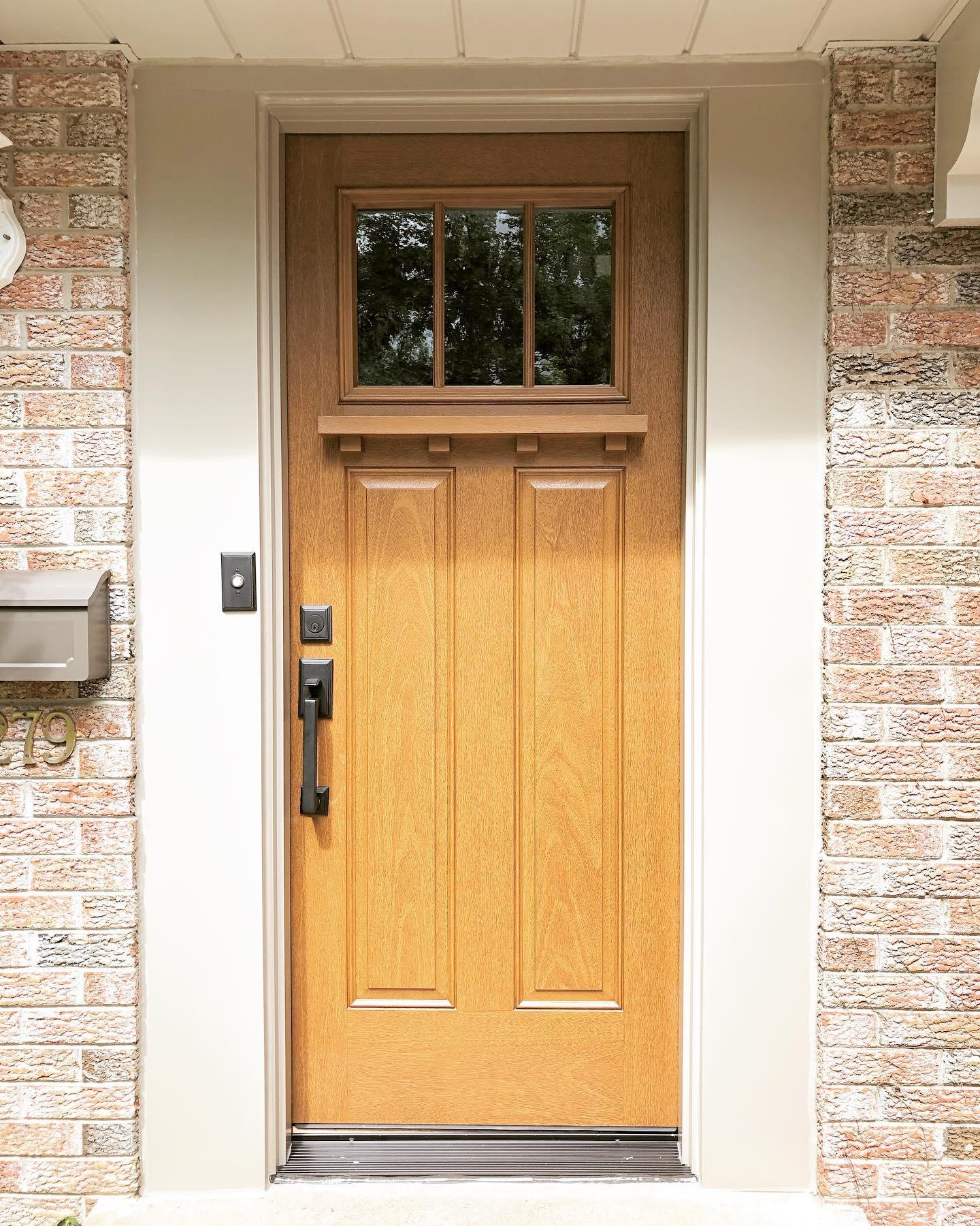 Craftsman style front door in fiberglass wood grain on brick house