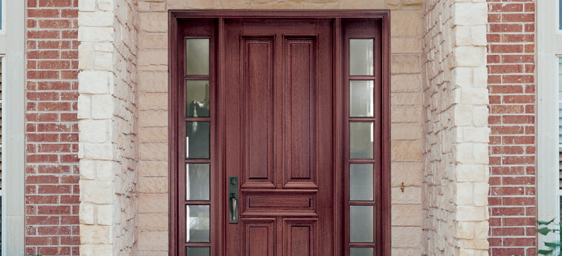 four panel traditional wood entry door with full light sidelights on each side