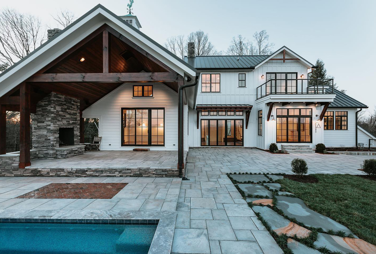 The exterior of a white farmhouse-style home with black windows and patio doors that overlook outdoor fireplace and pool.