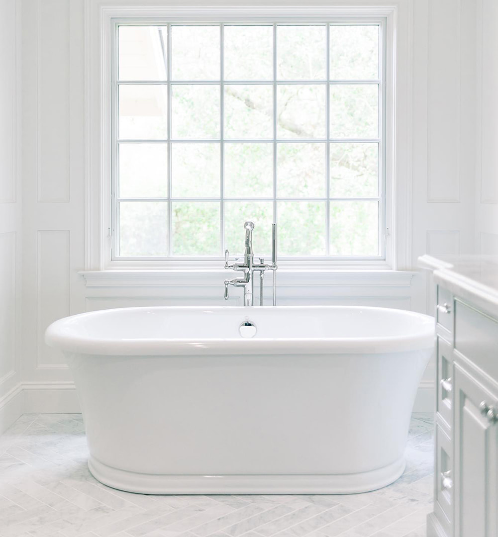 A traditional awning window with grilles over a white bathtub.