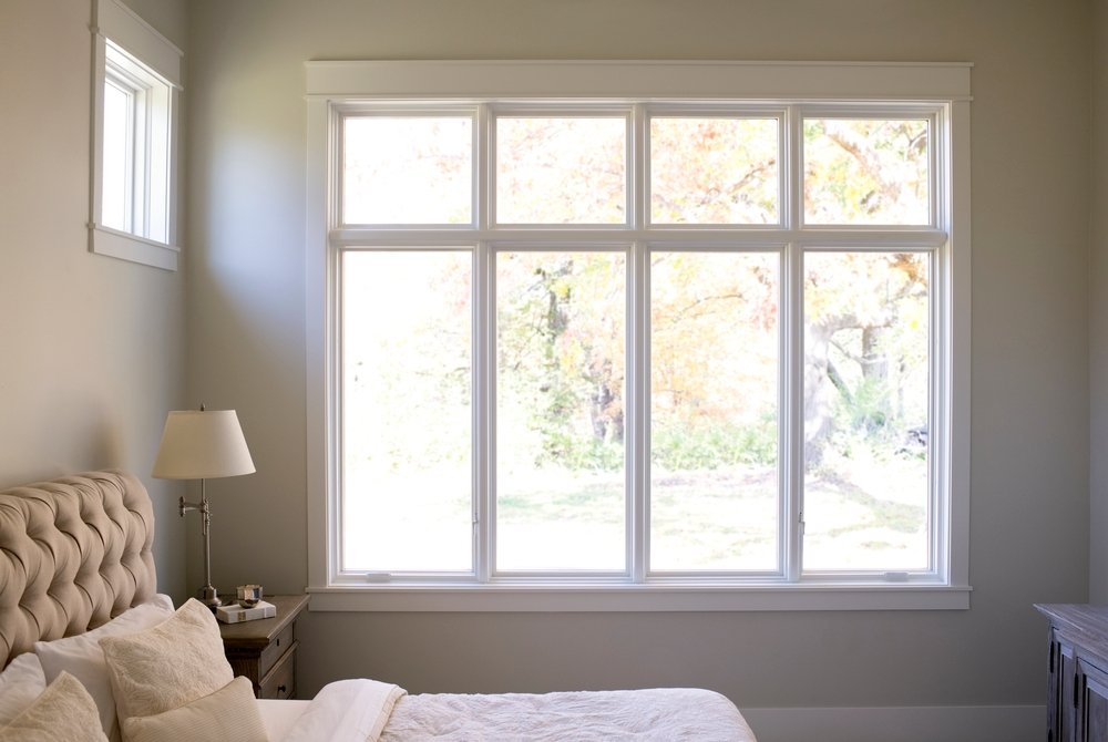 Row of four white windows with white trim in beige bedroom