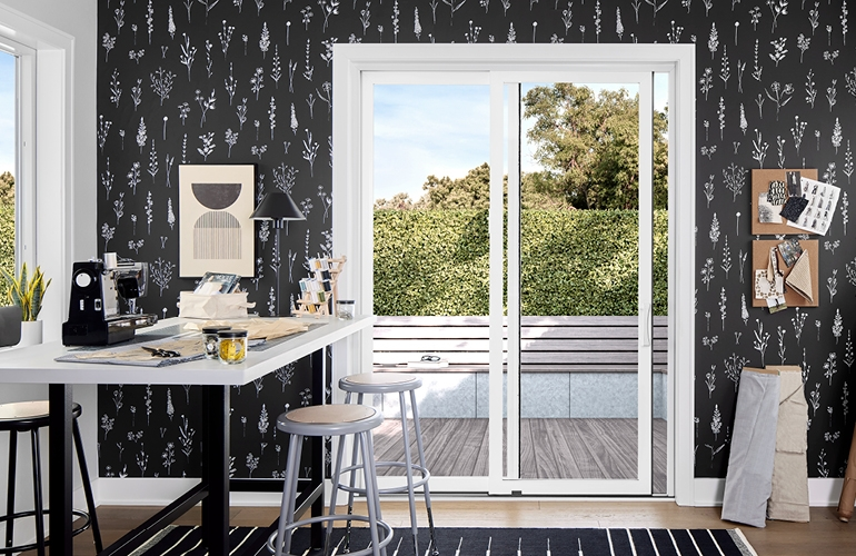 Sewing room with black patterned wallpaper and a white sliding door