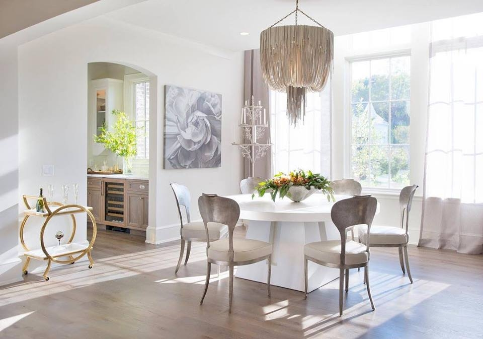Neutral dining room with white table, wood chairs, beaded chandelier and three tall picture windows light the room