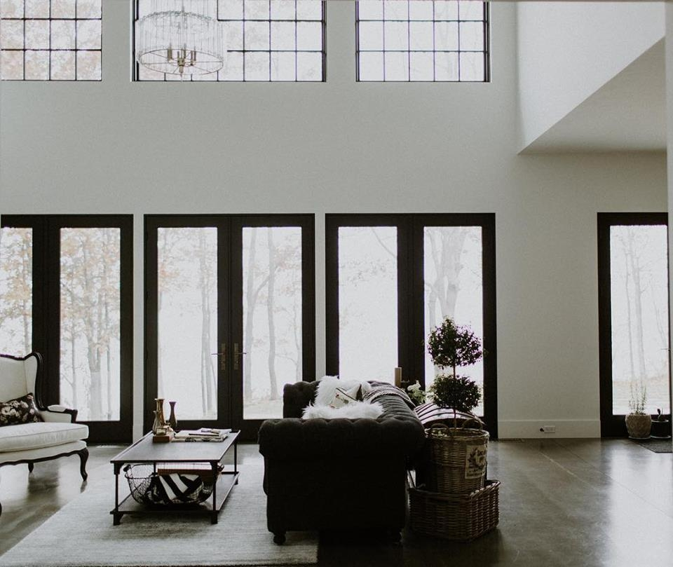 open concept living room with high ceilings and a wall of three black french doors