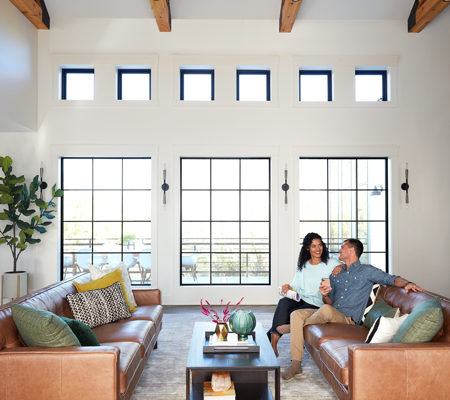 Couple sitting in living room with 3 black picture windows.