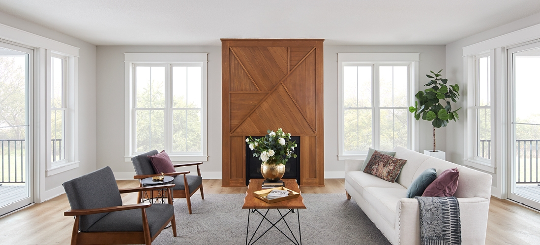 white encompass windows in a white living room with wood fireplace