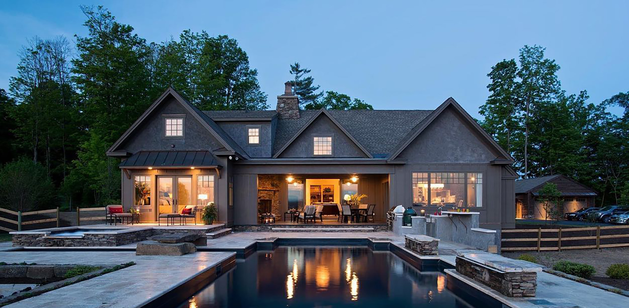 A farmhouse with gray windows and gray patio doors creates inviting exterior space by the pool.