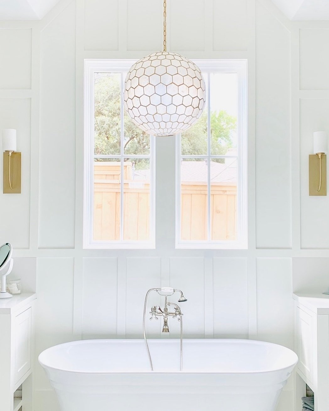 Freestanding bathtub with white picture windows above and a glass pendant light