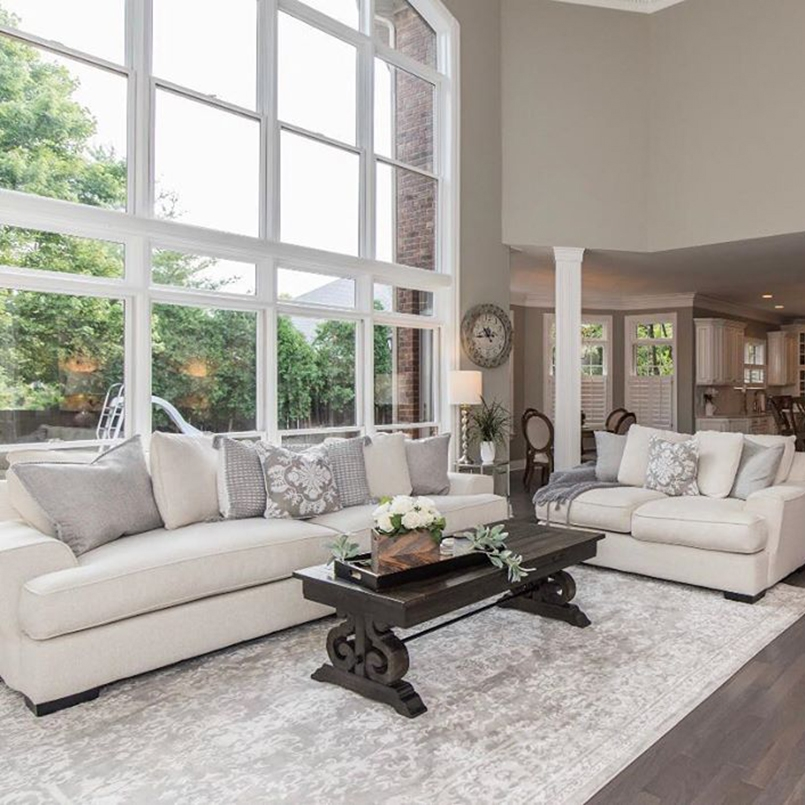 Neutral colored living room with white couches in front of floor-to-ceiling glass windows