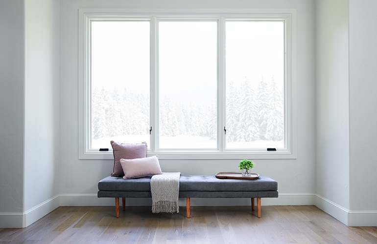 three white wood casement windows over a window seat