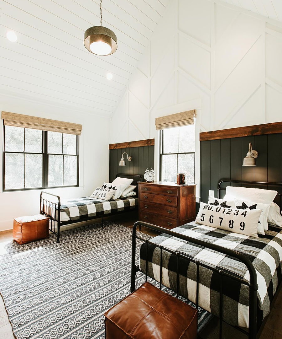 A farmhouse-style bedroom has two twin-size beds and black double-hung windows.