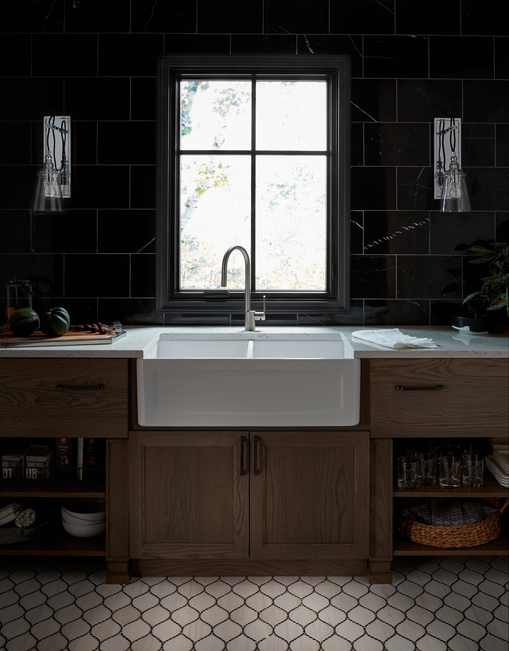 Black casement window with matte black hardware over apron sink and wood cabinets
