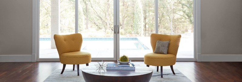 two yellow chairs in front of a pella sliding door