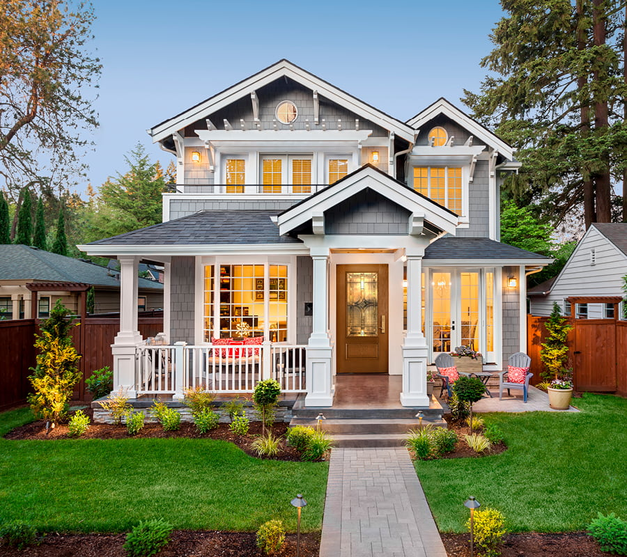 Two Story gray siding home with wood entry door and white framed windows with grilles