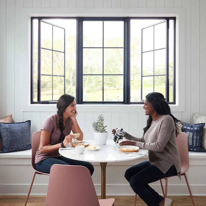 two women sitting at table by three lifestyle series casement windows