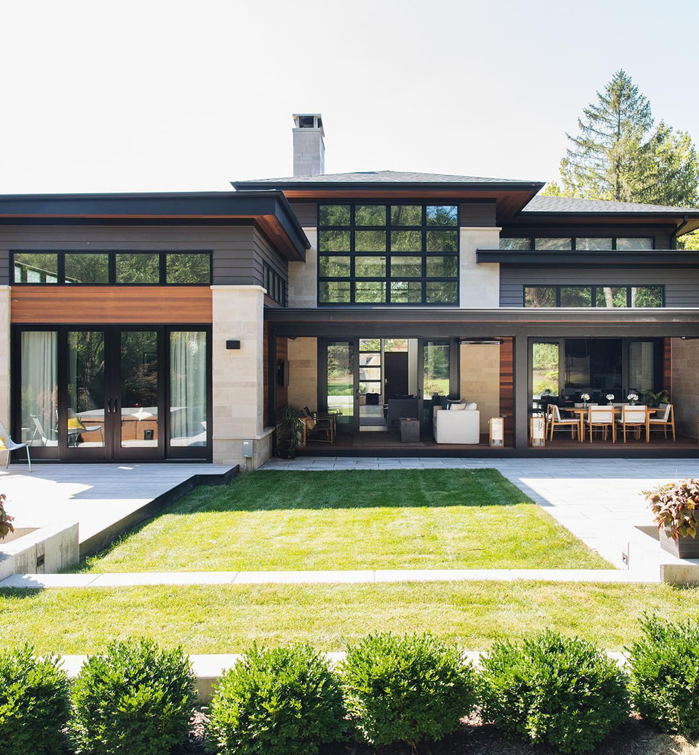 Modern and contemporary home features sliding patio doors and picture windows creating walls of glass across the back of the house.