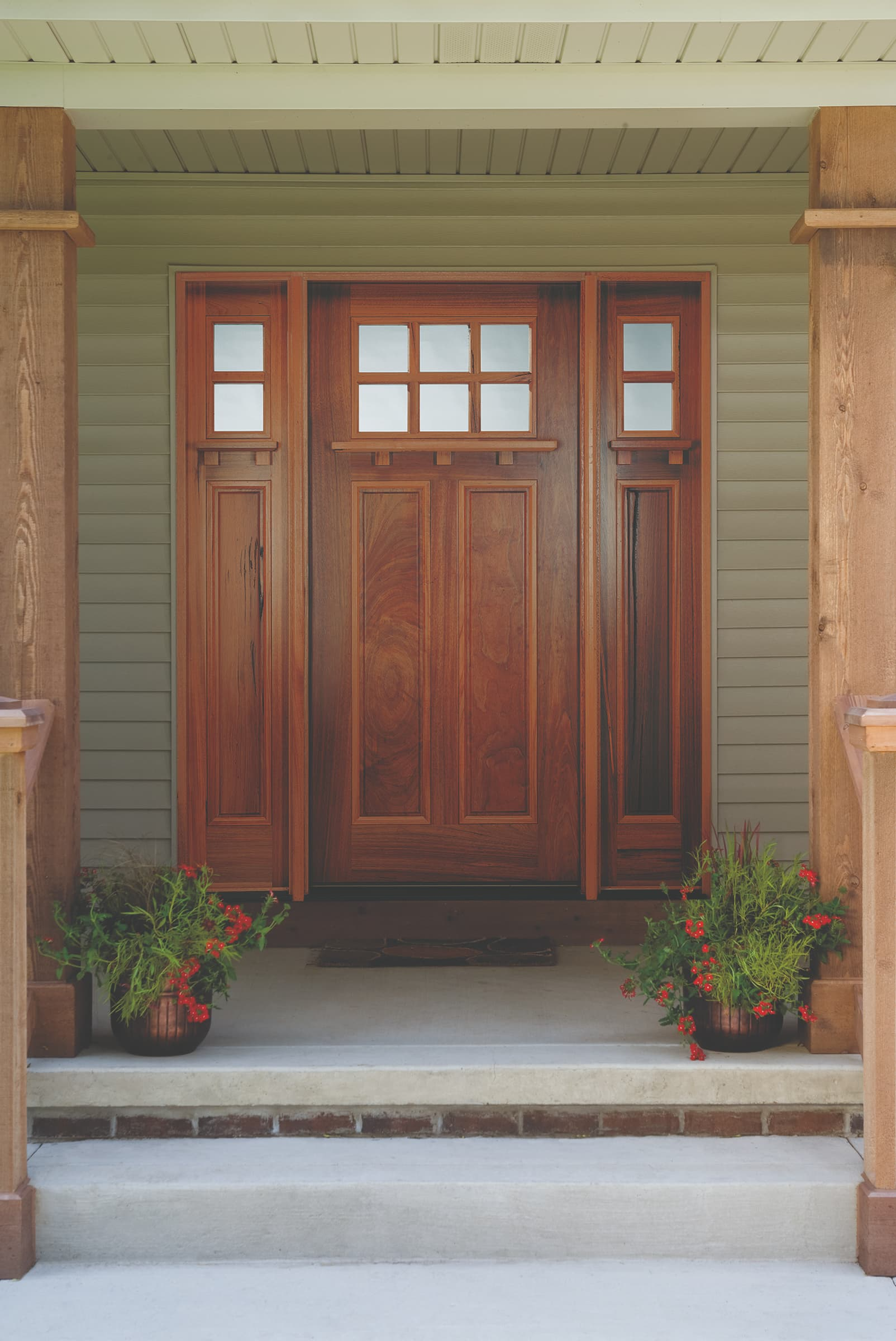 Craftsman style front door made of real wood set in inviting porch