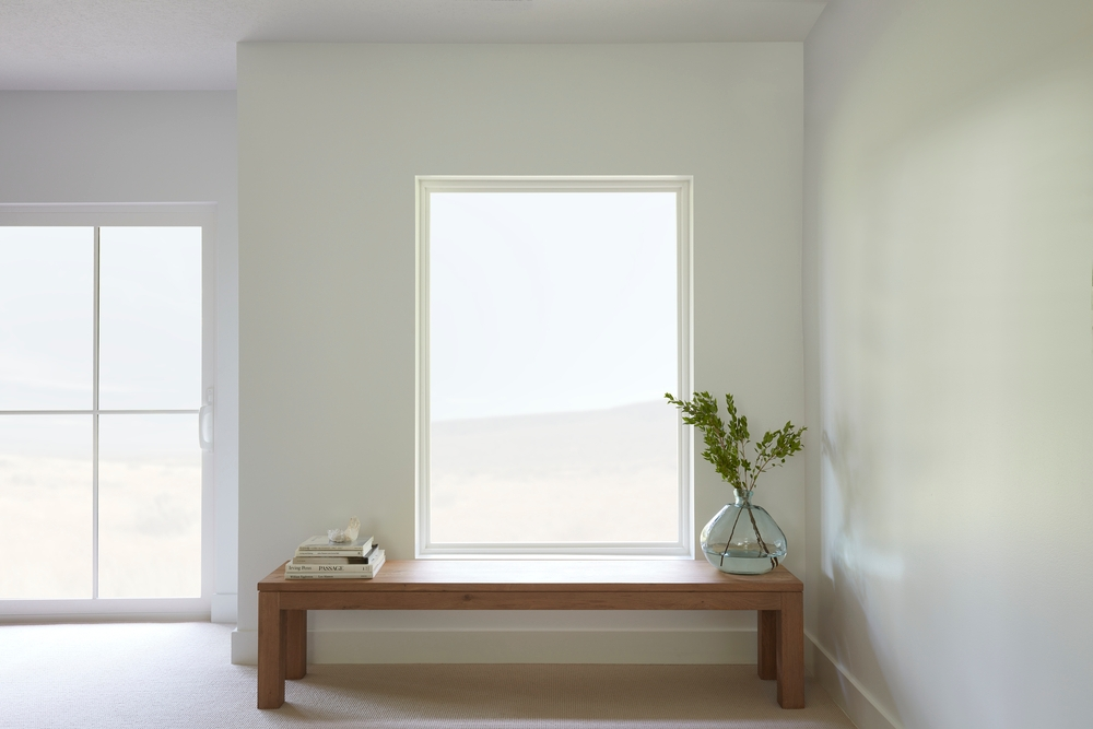 Large fixed window with bench underneath next to sliding patio door