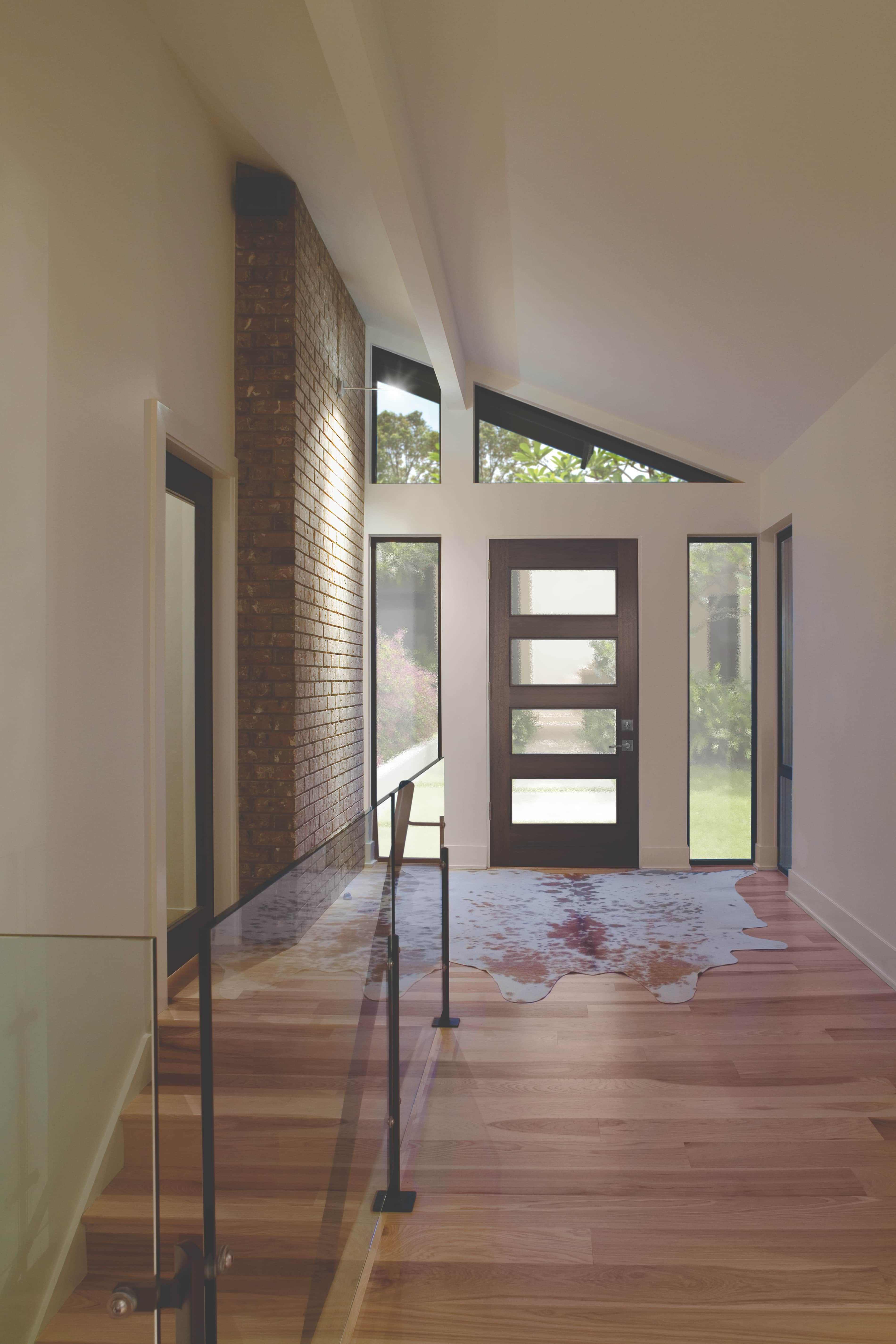 Stylish entryway with modern wood front door and angled ceiling