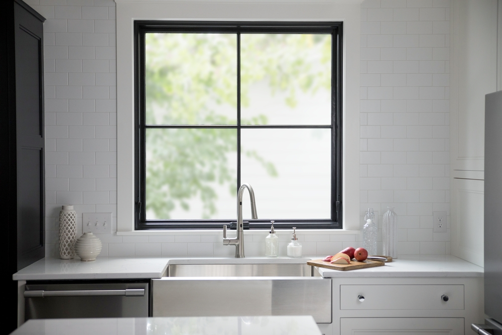 White kitchen counter with farmhouse sink and square black window directly above