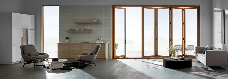 wood-framed bifold patio door in a contemporary living room with concrete floors
