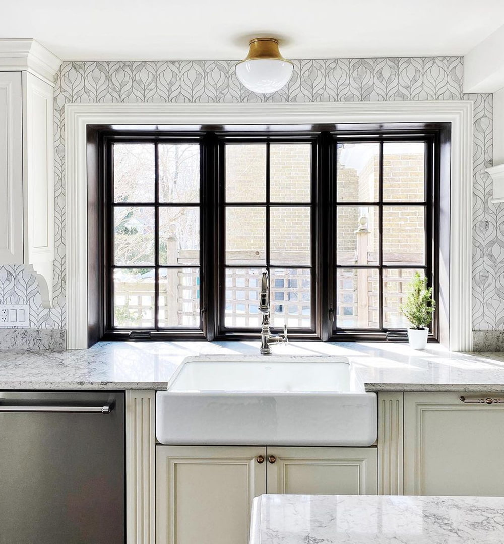 A black kitchen box window features two casement windows with a picture window in the middle.