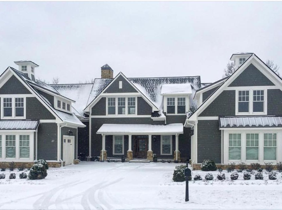 Gray farmhouse with white double-hung windows covered in snow