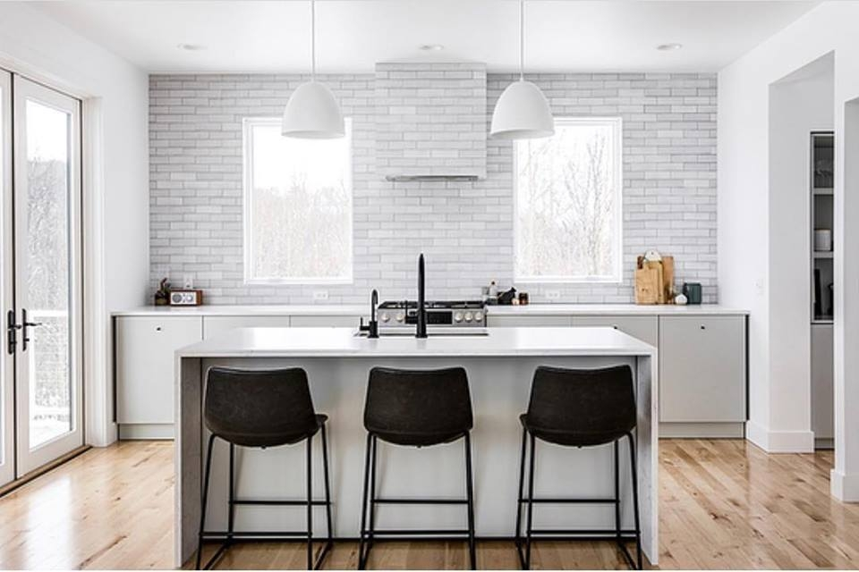 Two white casement windows above kitchen island with black barstools