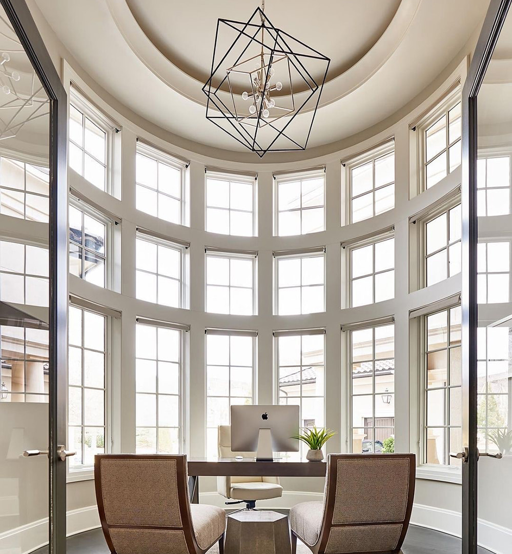 Office with curved walls features a mixture of casement and picture windows from the floor to the ceiling.