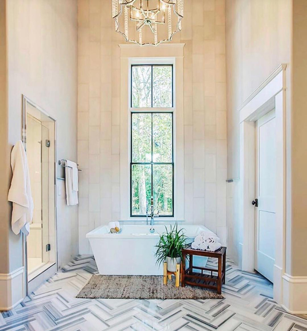 A modern and comtemporary bathroom with high ceilings and a chandelier features a bathtub with a tall black window above.