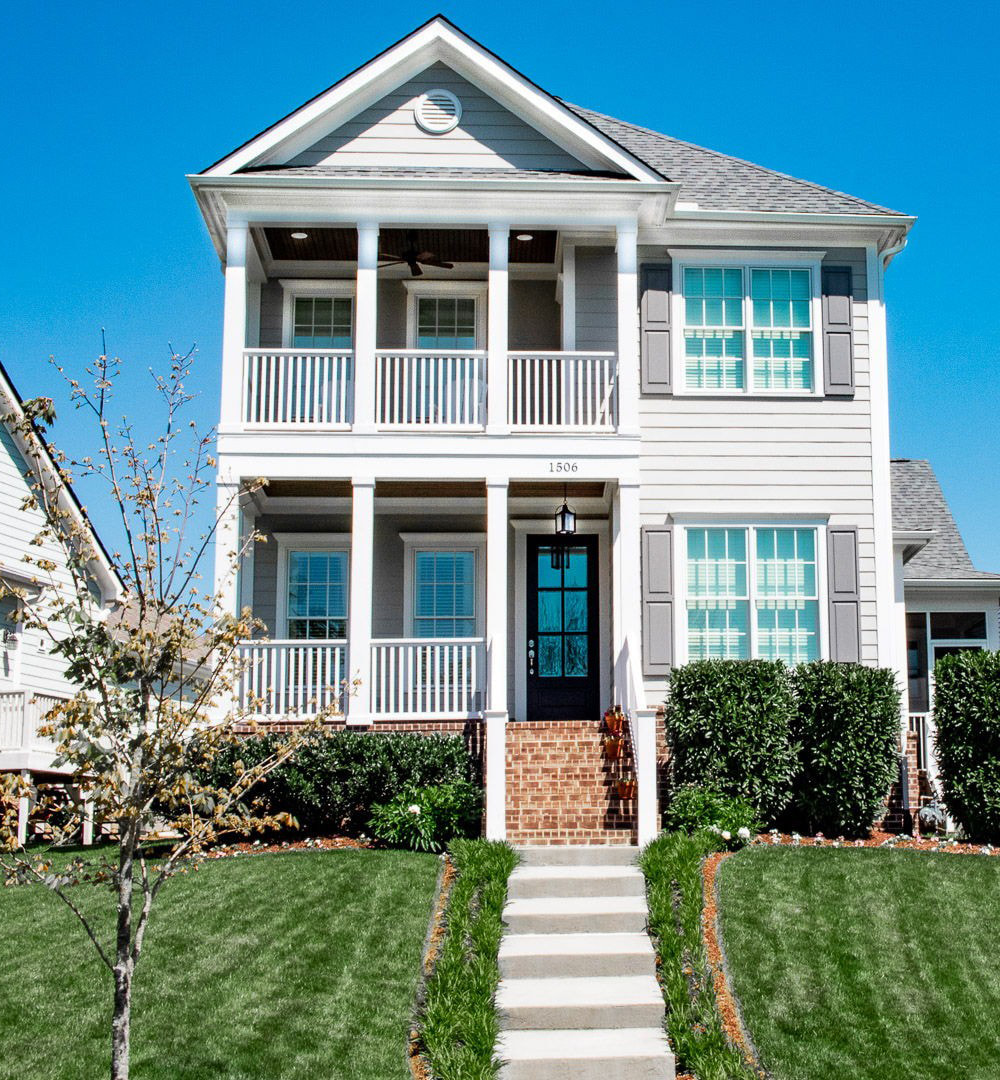 A two-story home features a brick stairway to the front door along with white double-hung windows that overlook a porch and balcony.