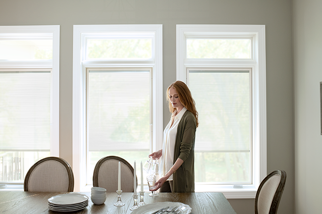 red-headed woman setting a table with three lifestyle series windows behind her