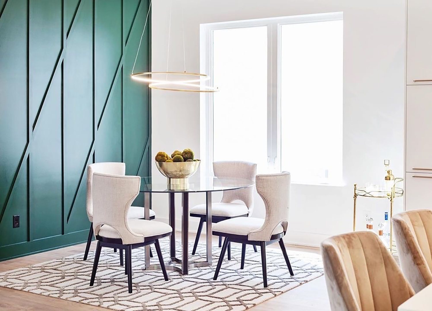 Contemporary dining room with bright colors and white casement windows behind the table.