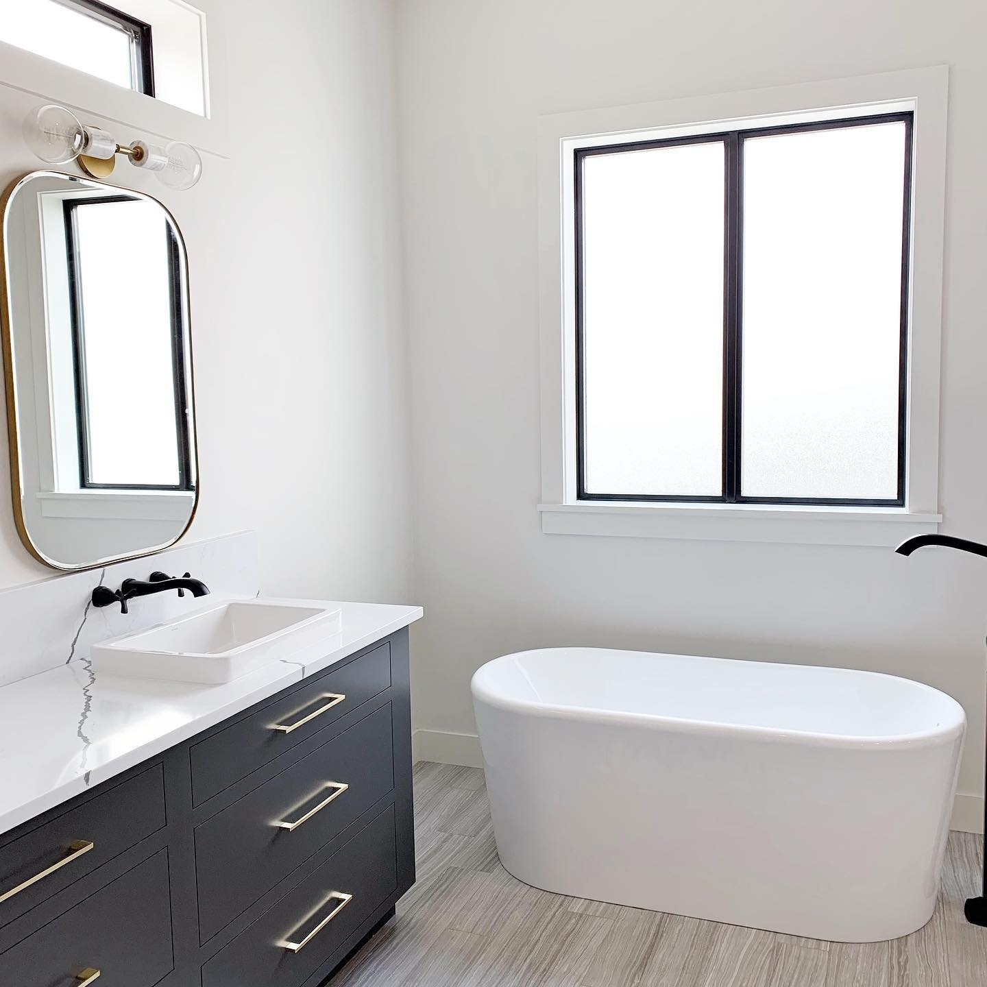 Black and white bathroom features white tub with black sliding window overhead