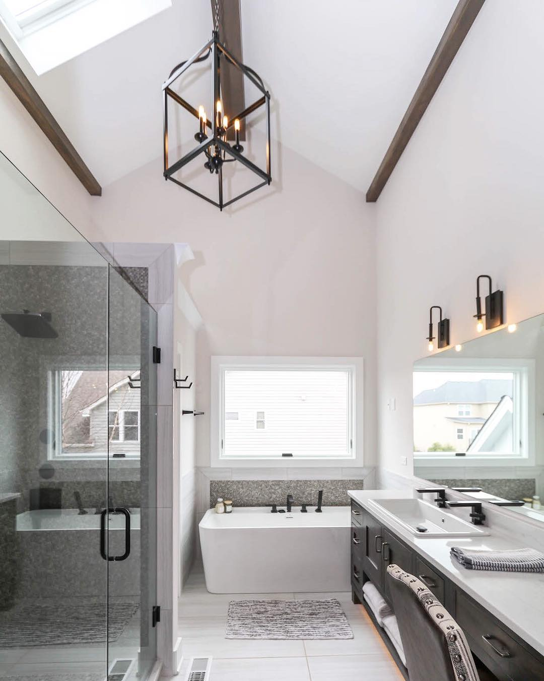 modern bathroom with glass shower and awning window over freestanding tub