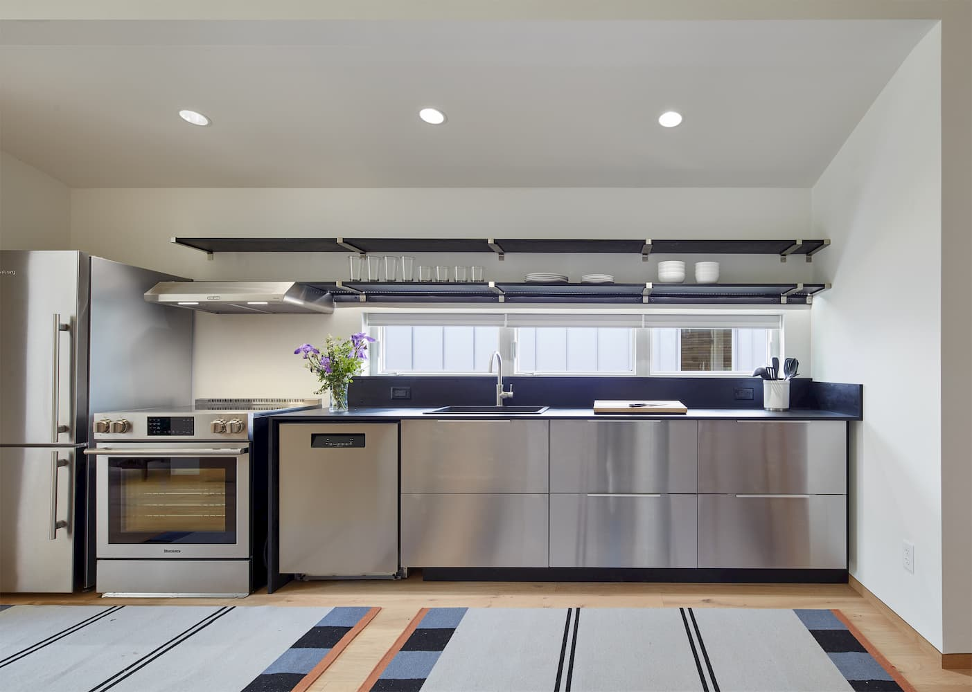 Industrial style kitchen with stainless steel appliances and cabinets with a long rectangle window above the counter top