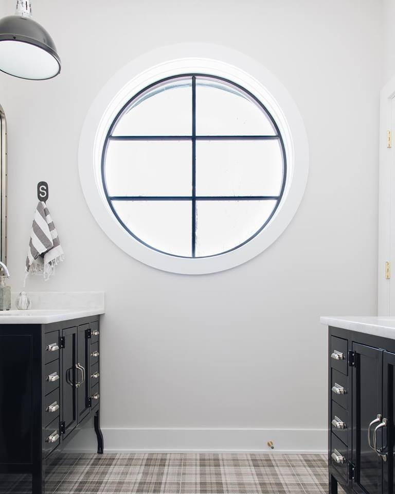 white bathroom with black vanities on either side and a large circle window in the middle