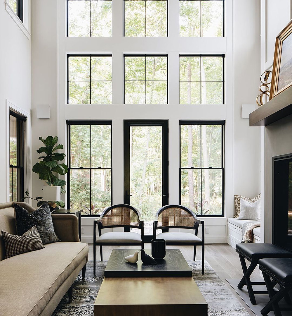 A modern contemporary living room features furniture up front with double-hung windows, picture windows and a patio door along the back wall.