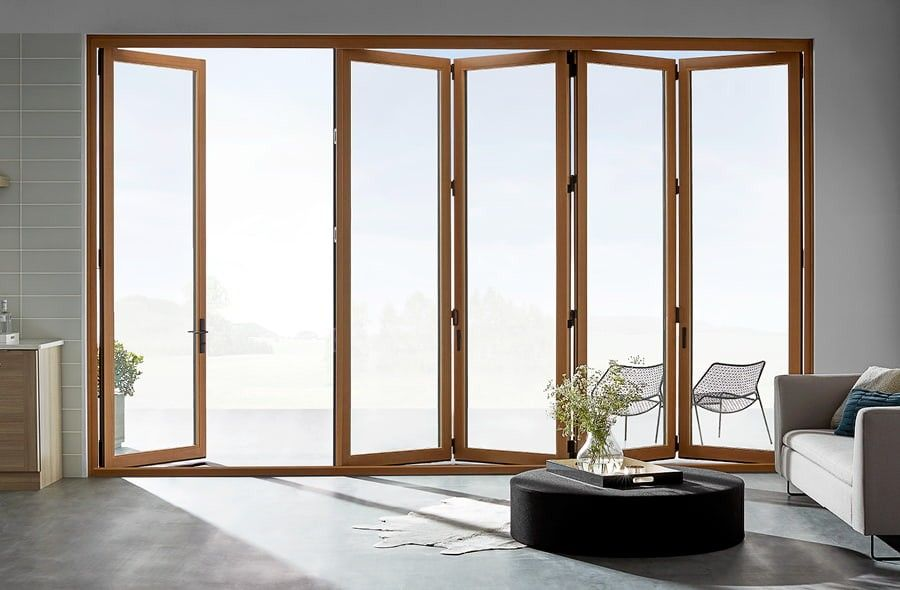 Interior view of light wood bifold doors slightly open to outside