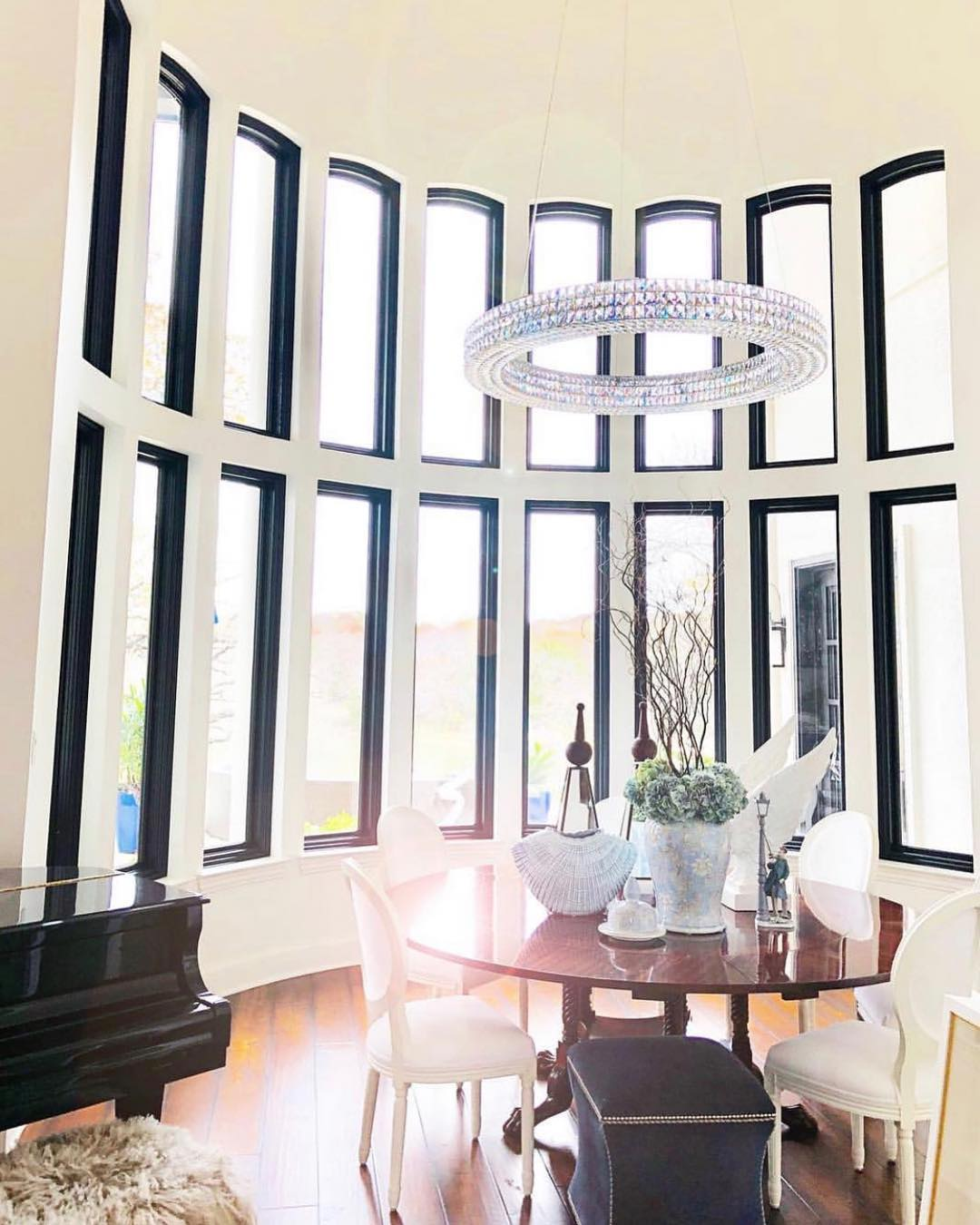 curved wall filled with black casement windows in a dining room