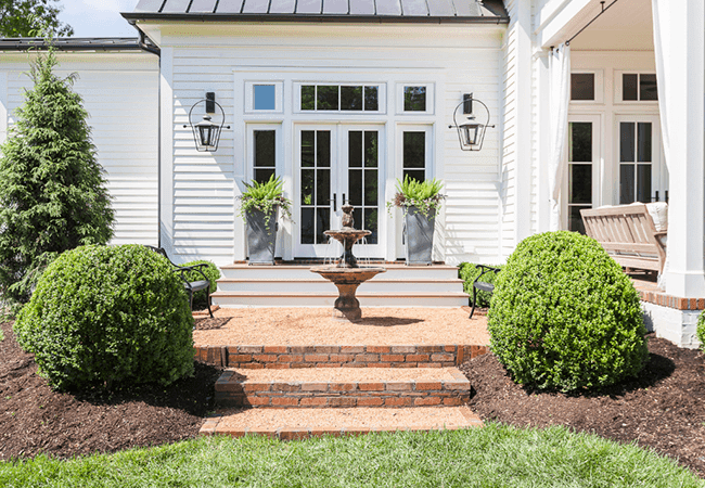 Backyard of white siding home with brick stairs, fountain and hedges.