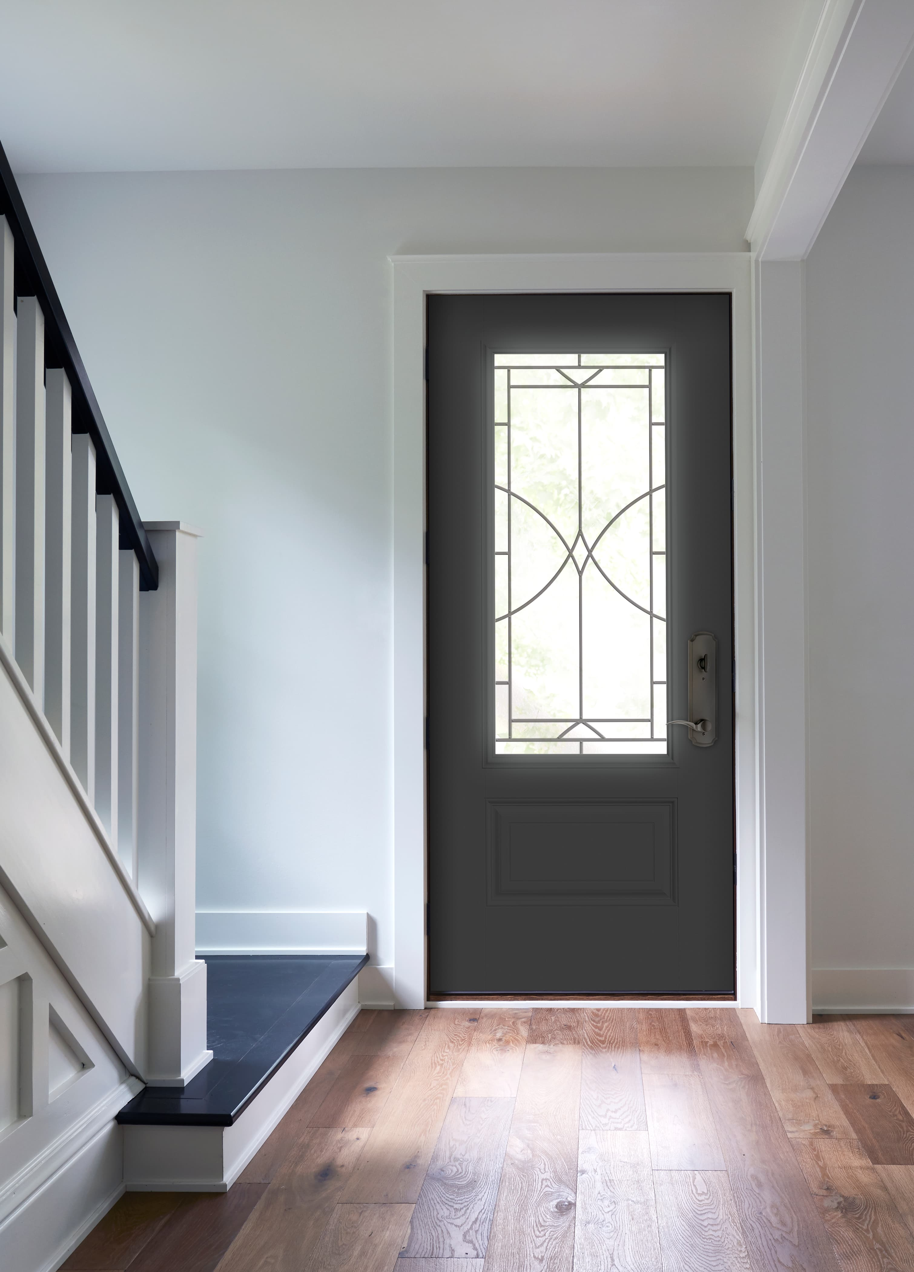 Black entry door with decorative glass and white trim